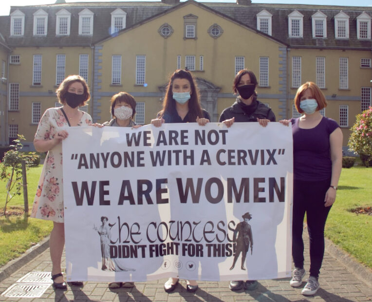 """Photo of women protesting outside the HSE head office holding a banner saying """"We are not 'Anyone with a cervix' WE ARE WOMEN"""" and a logo saying The Countess Didn't Fight For This"""
