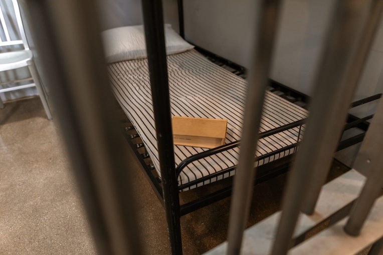 Photo of a prison bed as seen through bars