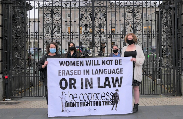 """Photo of four The Countess activists standing outside the Dail holding a banner saying """"Women will not be erased in language or in law - The Countess Didn't Fight For This"""""""
