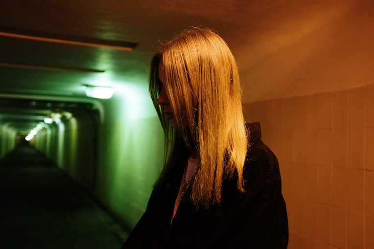 Photo of a teenager standing in a corridor with green and orange light
